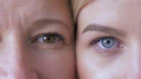 Comparaison de generations, yeux de maman caucasienne et fille à côté d'une une autre regardant ensemble la caméra