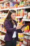 Comparaison en ligne de produit dans le supermarché Images stock