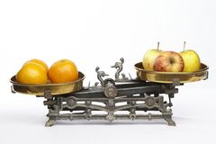 Compare apples to oranges. Apples and oranges on an old balance to visualisize the saw to compare apples to oranges royalty free stock images