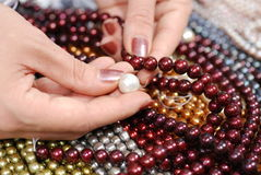 Compare pearls. On top of colorful freshwater pearl strands Royalty Free Stock Photography