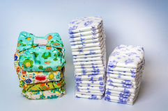 Compare reusable cloth diapers with pile of disposable diapers Royalty Free Stock Photo