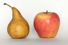 Comparer et pomme et une poire image stock