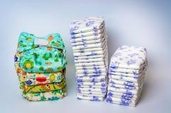 Comparez les couches-culottes réutilisables de tissu à la pile des couches-culottes jetables photo libre de droits
