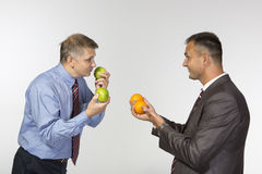 Comparing apples to oranges. Two business men are comparing apples to oranges Stock Photo