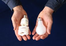 Comparing bulb types. One hand holding a compact fluorescent bulb, the other an incandescent bulb, to indicate comparison Stock Photography