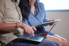 Comparing business data. Colleagues comparing financial reports on laptop and digital tablet royalty free stock photos