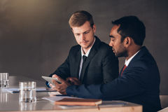 Comparing digital notes in the boardroom Stock Photo