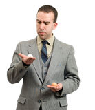 Comparing Eggs. Young businessman comparing a white egg and a brown egg; symbolic for different business plans stock photography