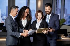 Comparing financial reports. Smiling multi-ethnic business team comparing financial reports of their departments at meeting royalty free stock images