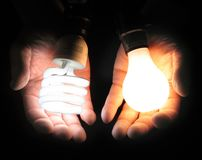 Comparing fluorescent and incandescent light bulbs. One hand holding a compact fluorescent bulb, the other an incandescent bulb, to indicate comparison, bulbs Royalty Free Stock Photos