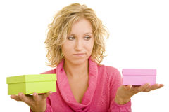 Comparing gifts. Young woman with a pink pullover compares two gifts in her hands royalty free stock photography