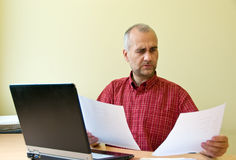 Comparing sales. Office worker working at the desk with sale reports royalty free stock image