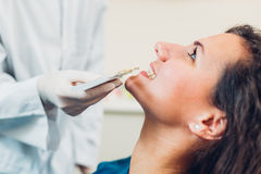 Comparing tooth. Dentist comparing woman tooth using a shade guide Stock Images