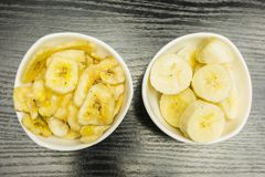 Comparison of bowls with fresh and dried banana. View from above Stock Image