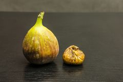 Comparison of fresh and dried fruit fig. Comparison of fresh and dried fruit fig on a dark wooden table Royalty Free Stock Image
