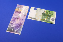 Comparison of money. Comparison of Swiss francs and euros with place for text lying on blue background Royalty Free Stock Images