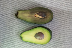 Comparison of opposites bad and good condition. Half the spoiled and good avocado. Comparison of opposites royalty free stock photo