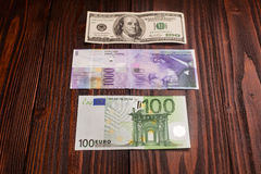 Comparison of Swiss francs dollars and euros. On wooden table Royalty Free Stock Photos