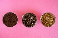 Comparison of three types of coffee in one picture: roasted beans, ground, soluble granulated. In round glass bowls on a pink. Background. View from above royalty free stock image