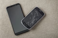 Comparison of two black mobile phones, old cellphone with cracked screen and new modern on light cloth copy space background. Technology progress and royalty free stock image