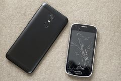 Comparison of two black mobile phones, old cellphone with cracked screen and new modern on light cloth copy space background. Technology progress and royalty free stock photo