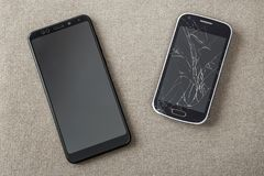 Comparison of two black mobile phones, old cellphone with cracked screen and new modern on light cloth copy space background. Technology progress and stock photography