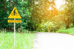 Comparta la señal de tráfico con el ciclista que la muestra del montar a caballo de la bici está en la aguamiel Imagenes de archivo
