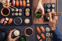 Compartiendo y comiendo la comida del sushi fotografía de archivo libre de regalías