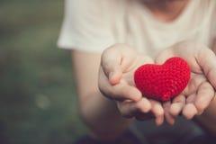 Compartilhando da cor vermelha do amor e do coração na mão das mulheres imagens de stock royalty free