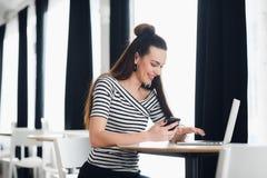 Compartilhando de boas notícias de negócios Jovem mulher atrativa que fala no telefone celular e que sorri ao sentar-se no seu tr imagens de stock