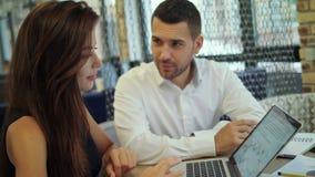 Compartilhando de suas ideias Jovem mulher de sorriso que trabalha no portátil quando homem que senta-se perto dela na área de re filme