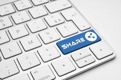 Compartilhe do botão azul com um ícone da rede em um teclado isolado branco fotos de stock