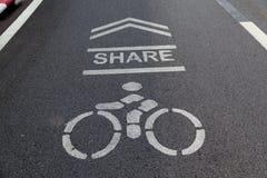 Compartilhe por favor de pistas da bicicleta para motociclistas as bicicletas assinam dentro o parque Fotos de Stock
