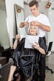 Compartimento da leitura da mulher ao ter o corte de cabelo imagem de stock