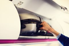 Compartimento di bagaglio a mano con le valigie in aeroplano Le mani decollano il bagaglio a mano Il passeggero ha messo la cabin Immagini Stock