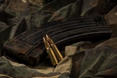 Compartimento e balas oxidados de AK-47 no fundo de matéria têxtil da camuflagem Imagem de Stock
