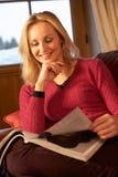Compartimento envelhecido médio da leitura da mulher no sofá fotos de stock royalty free
