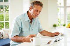 Compartimento envelhecido meio da leitura do homem sobre o café da manhã fotos de stock