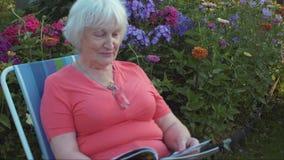 Compartimento superior da leitura da mulher no jardim no dia de verão video estoque
