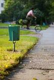 Compartimiento de basura de la ciudad y ciclista Imágenes de archivo libres de regalías