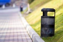 Compartimiento de basura negro del metal en parque con el fondo soleado borroso Foto de archivo
