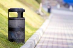 Compartimiento de basura negro del metal en parque con el fondo soleado borroso Fotos de archivo libres de regalías