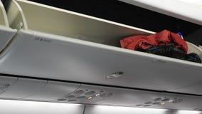Compartimiento de equipaje en el aeroplano con bulto de mano adentro Compartimiento de equipaje del aeroplano