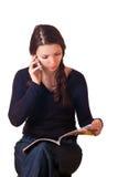 Compartimiento de la lectura de la muchacha y el hablar por el teléfono. Imágenes de archivo libres de regalías