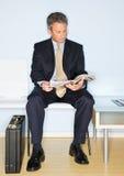 Compartimiento de la lectura del hombre de negocios en sala de espera Foto de archivo libre de regalías