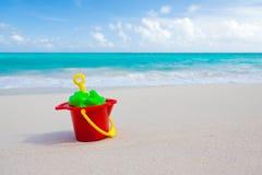 Compartimiento y juguetes en la playa Foto de archivo