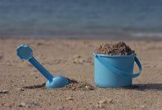 Compartimiento y pala en la arena de la costa Fotografía de archivo