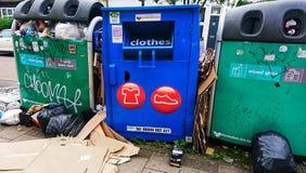 Compartimientos rubish de la calle y un compartimiento de la ropa para los pobres foto de archivo