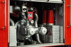 Compartment of rolled up fire hoses on a fireengine. Emergency s Stock Photos