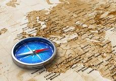 Compas bleu en métal sur la carte de Vieux Monde Photographie stock